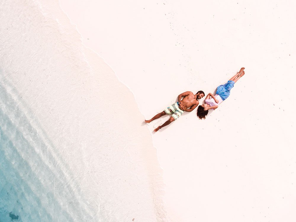 Tourist couple on the beach shot with drone